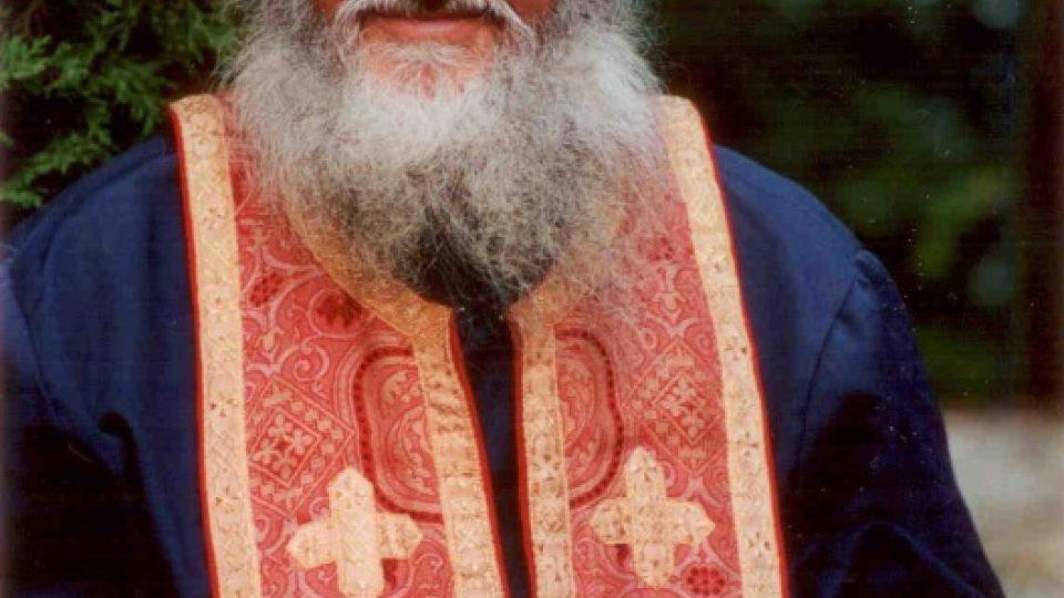 Rumunský kněz má na sobě modrou kleriku, červený epitrachil a z listů papíru před sebou se modlí za jednotlivé lidi, jejichž jména tam dostal napsaná.